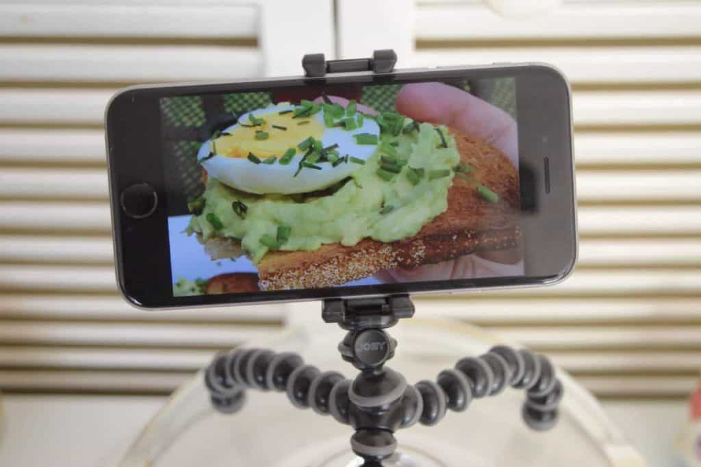 Phone on a GorillaPod tripod featuring a picture of avocado and egg toast