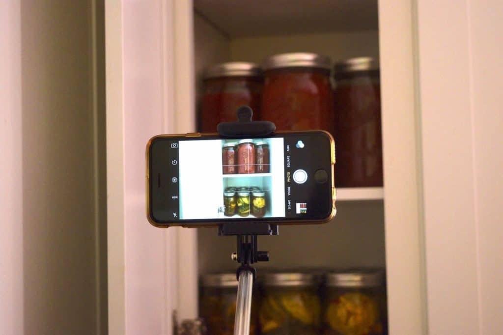 Phone mounted on a selfie stick taking a photo of a kitchen cabinet