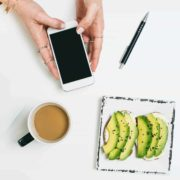 Overhead shot of coffee, avocado and a hand holding an iPhone
