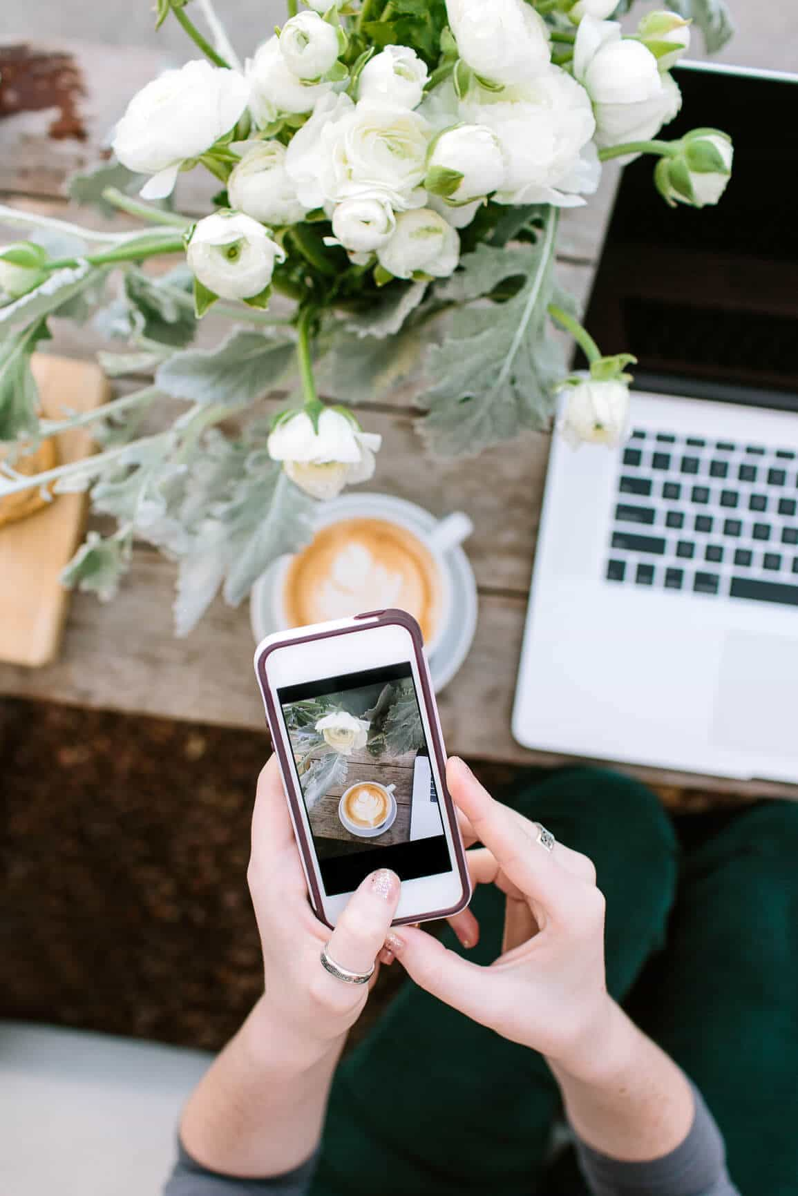 Woman taking iphone photo of her coffee on beautiful table with flowers and laptop.